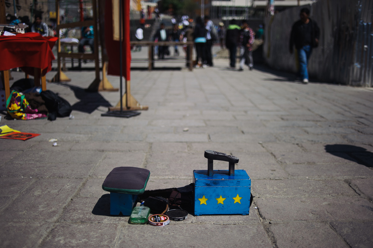 "The shoe-shining kit of a ""lustradore"" sits in the San Francisco plaza in La Paz, Bolivia. All of the shoe polish and brushes fit into the box, which is topped by the small stool the lustradores sit on whilst working."