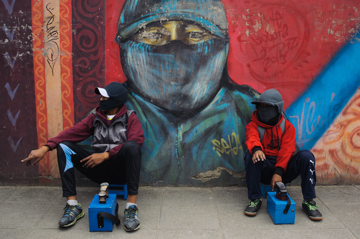 "Ruben Flores (13) (right) and his friend, Roberto (15) (left), sit in a passageway covered with graffiti of shoe-shiners in La Paz, Bolivia. ""Lustradores"" (shoe-shiners) are stigmatised in the city, forcing the vast majority to wear balaclavas covering their faces."