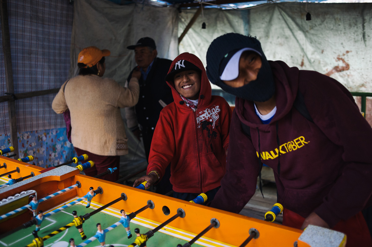 "Ruben Flores (13, centre) and his friend, Roberto (15, right), play table-football in an outdoor ""fair"" in La Paz, Bolivia. The boys took the afternoon off from working as shoe-shiners, and spent some of their earnings on recreation."