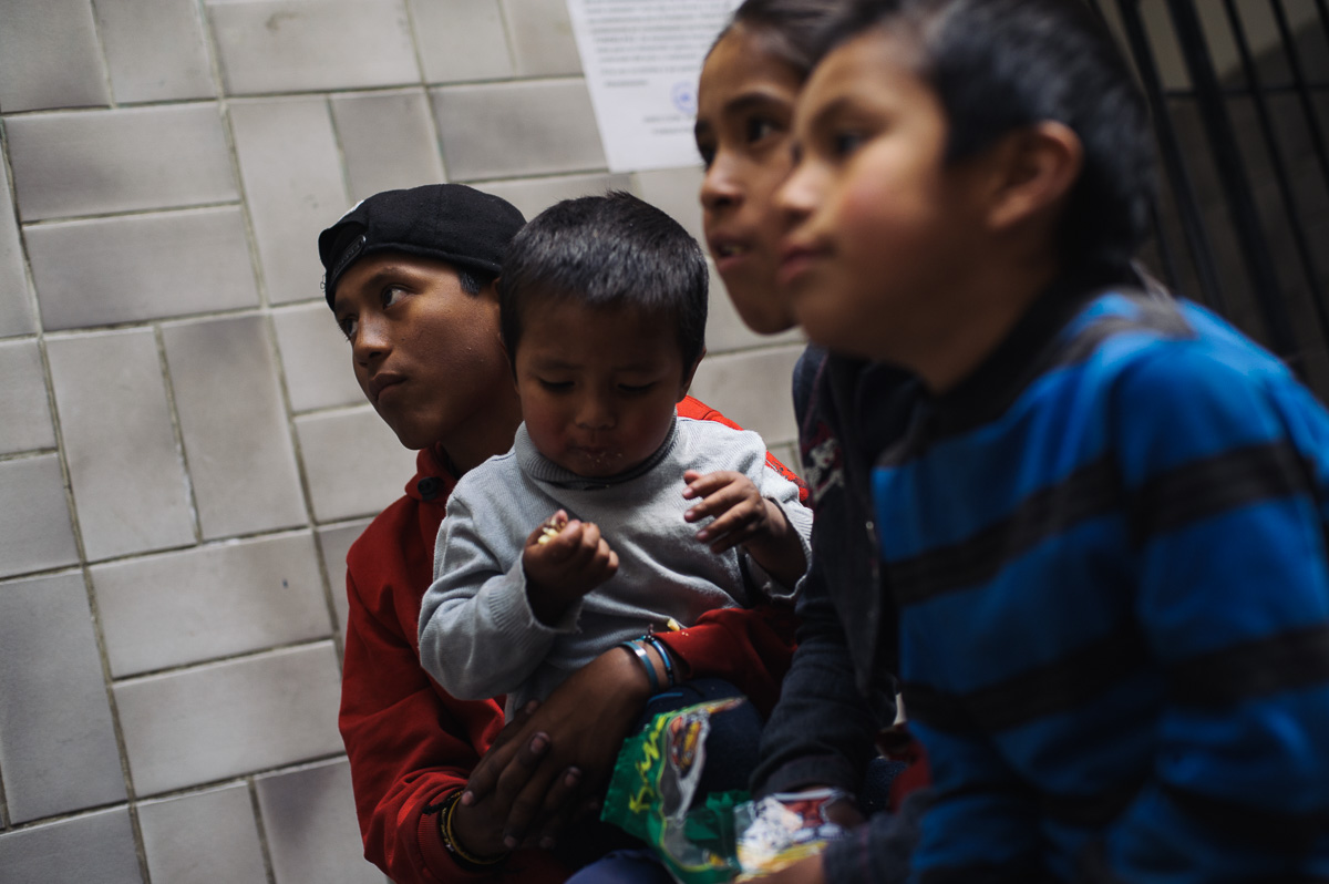"Ruben Flores (13) sits with his younger siblings as they watch television in the ""New Day Foundation"" centre where the family lives in La Paz, Bolivia. Ruben works as a shoe-shiner, and his income helps to provide for the family when times are tough."