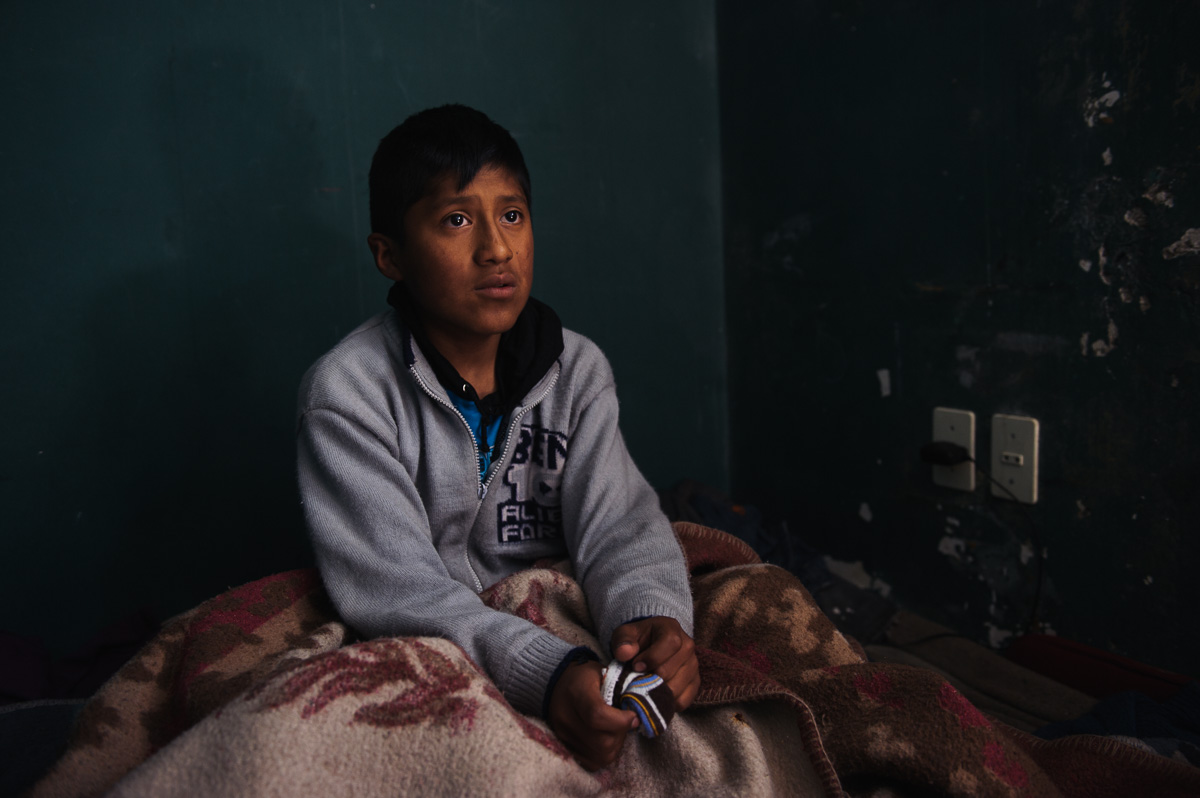 "Ruben Flores (13), a shoe-shiner in La Paz, sits in the bed he shares with his four siblings and parents at the ""New Day Foundation"" association in La Paz, Bolivia, on December 5, 2014. Ruben works as a shoe-shiner in the Bolivian capital, helping to support his family with his earnings."