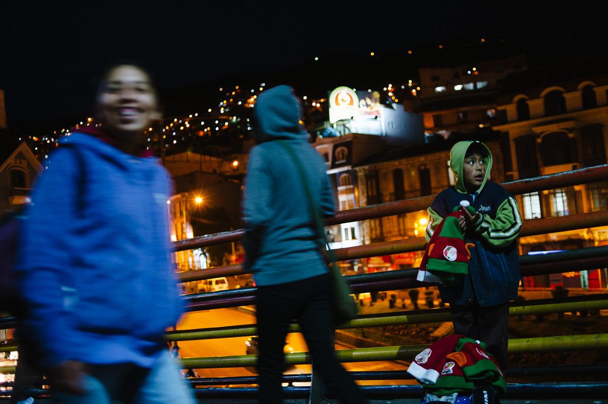 "A young boy sells ""Santa"" hats on a pedestrian bridge at night in La Paz, Bolivia."