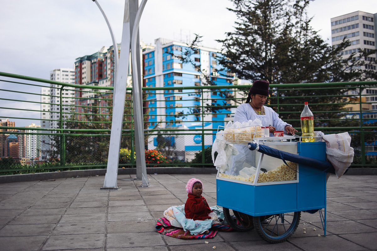 A lady works at a pop-corn stand as her young child sits on the floor in La Paz, Bolivia. Many parents take their young children with them when they work.