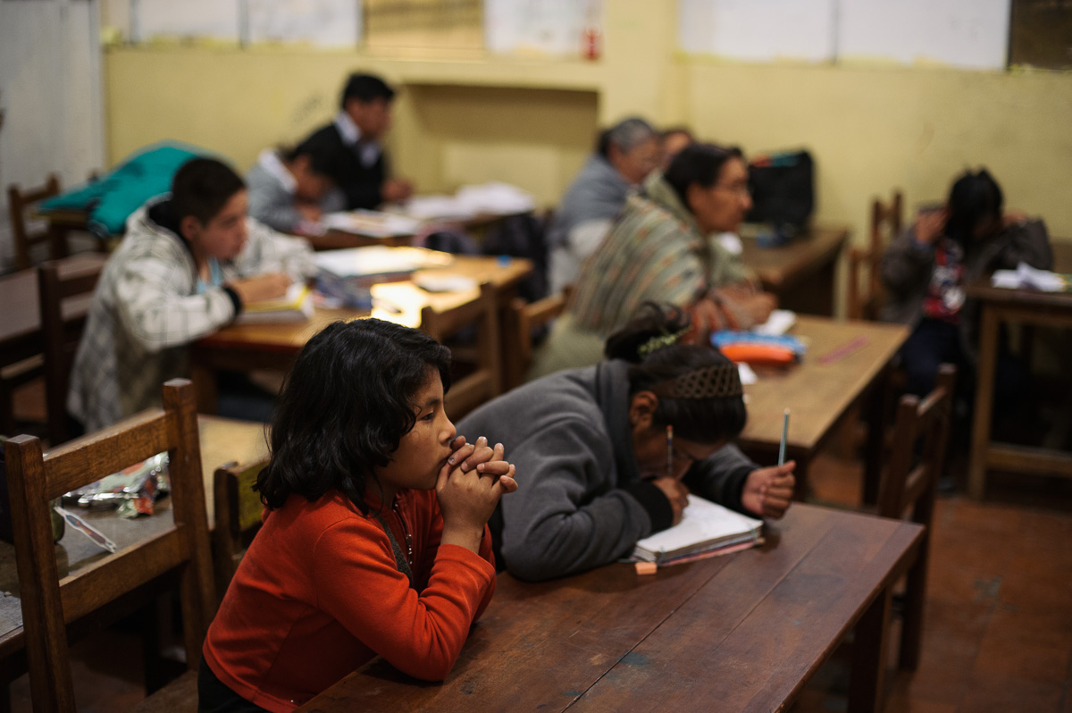 Pupils sit during a night-school class in La Paz, the Bolivian capital. The Bolivian law dictates that child workers must still attend school, and many children in this neighbourhood attend nightschool to allow them to work during the day. The children sit alongside adults who are belatedly getting a primary education.