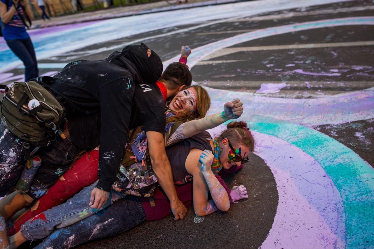 "Irena Stezijovska (28) [top] and Anna Krkulj (28) [bottom] celebrate with other activists as part of the ""Colourful Revolution"", having just finished a protest outside parliament in Skopje, Macedonia, on June 10, 2016. On the road, the group had painted a large ""8"", counting down the number of days left to an ultimatum given to the government."