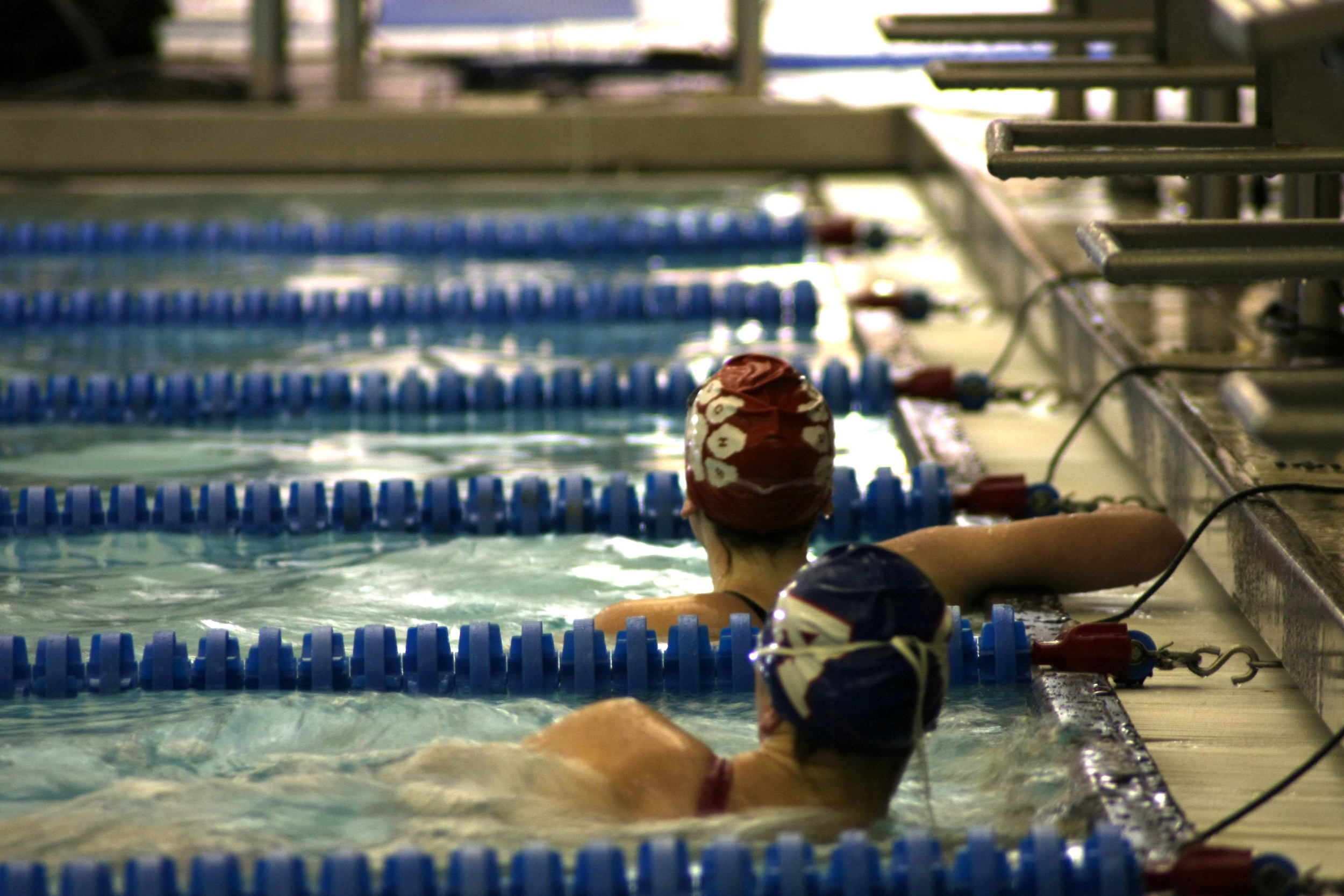 This is a picture I took just Tuesday.  There was a swim meet going on and I decided to check out my sports photography skills.  I shot this on my Canon 40 D with a 70-300mm telephoto lens.  Lighting was really dim in the pool area so I had to shoot on a lower shutter speed.  I was running into a lot of camera shake but managed to capture this shot at the end of one of the meets.  I like the depth of field and how the background drops off after the swimmers.