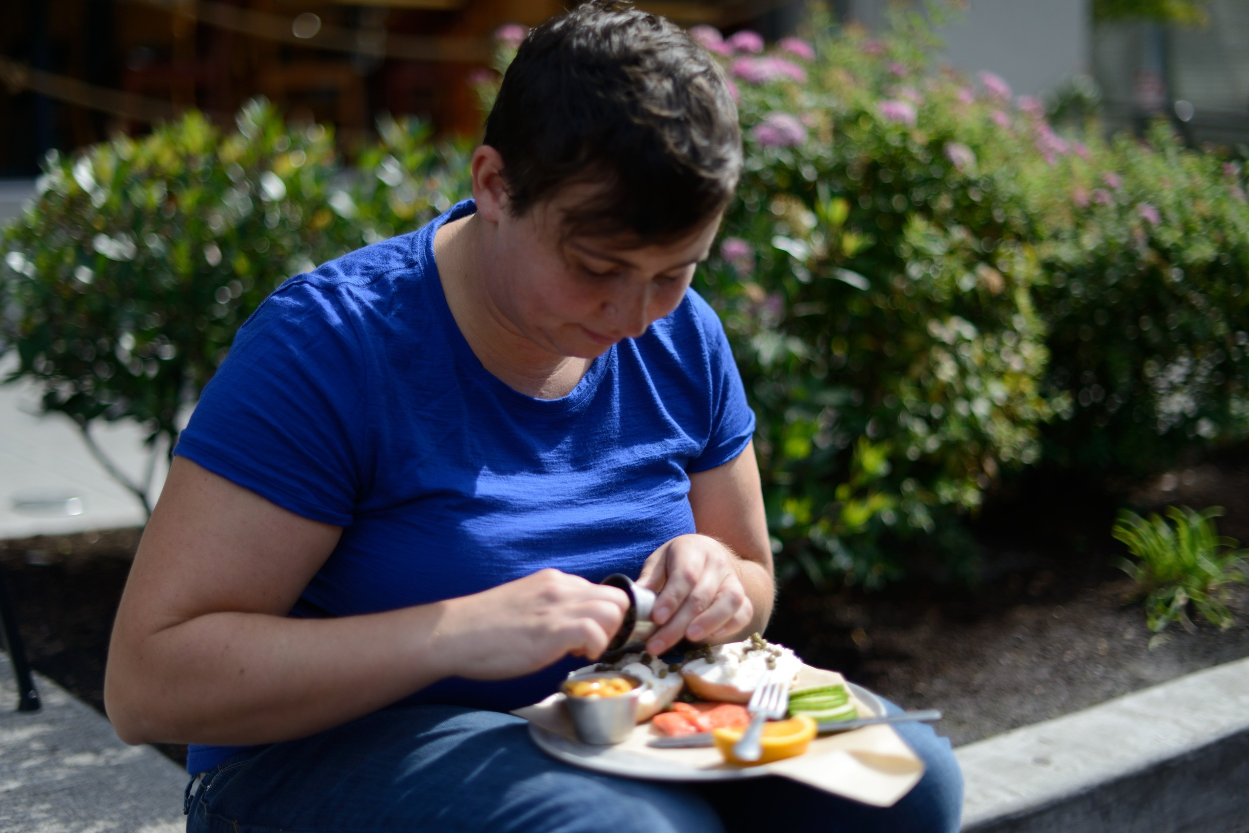 Employee Domonique Juleon takes a break from park(ing) day organizing to enjoy bagel and lox from partners Eltana.
