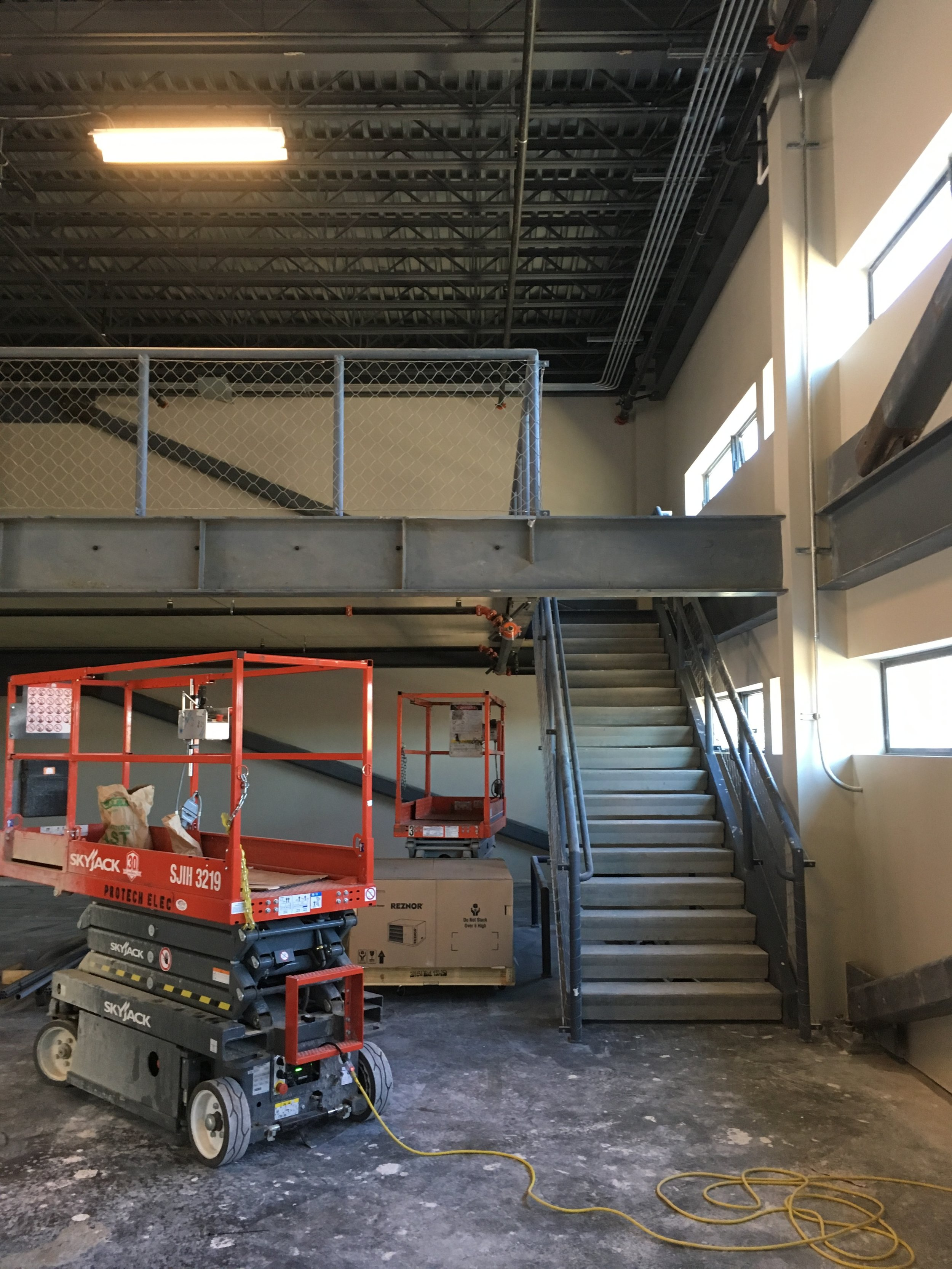 In progress T-I, including CLT mezzanine, stair construction, stainless steel mesh guardrail.