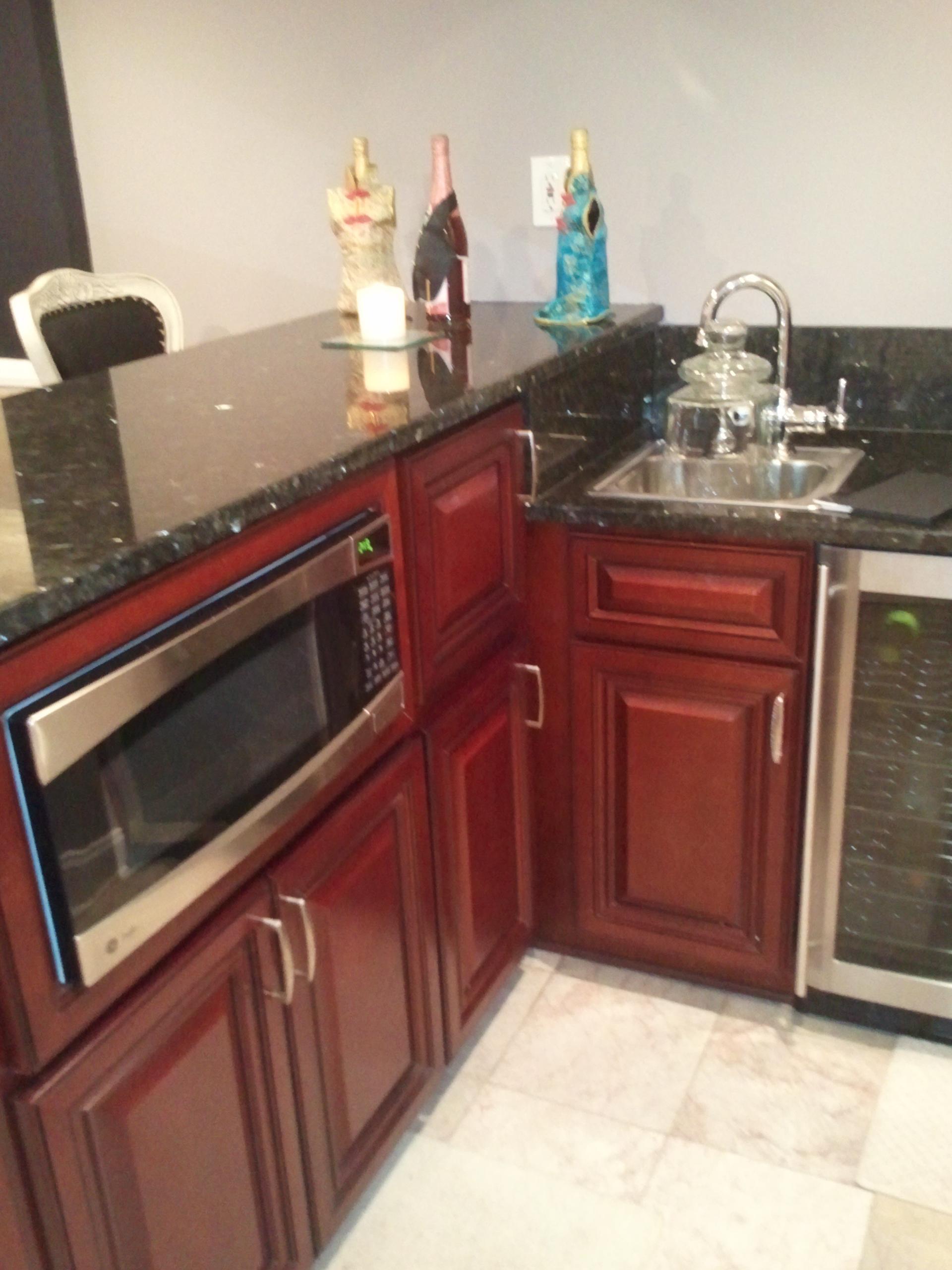 A bar custom builtto include a microwave, asink and a fridge.