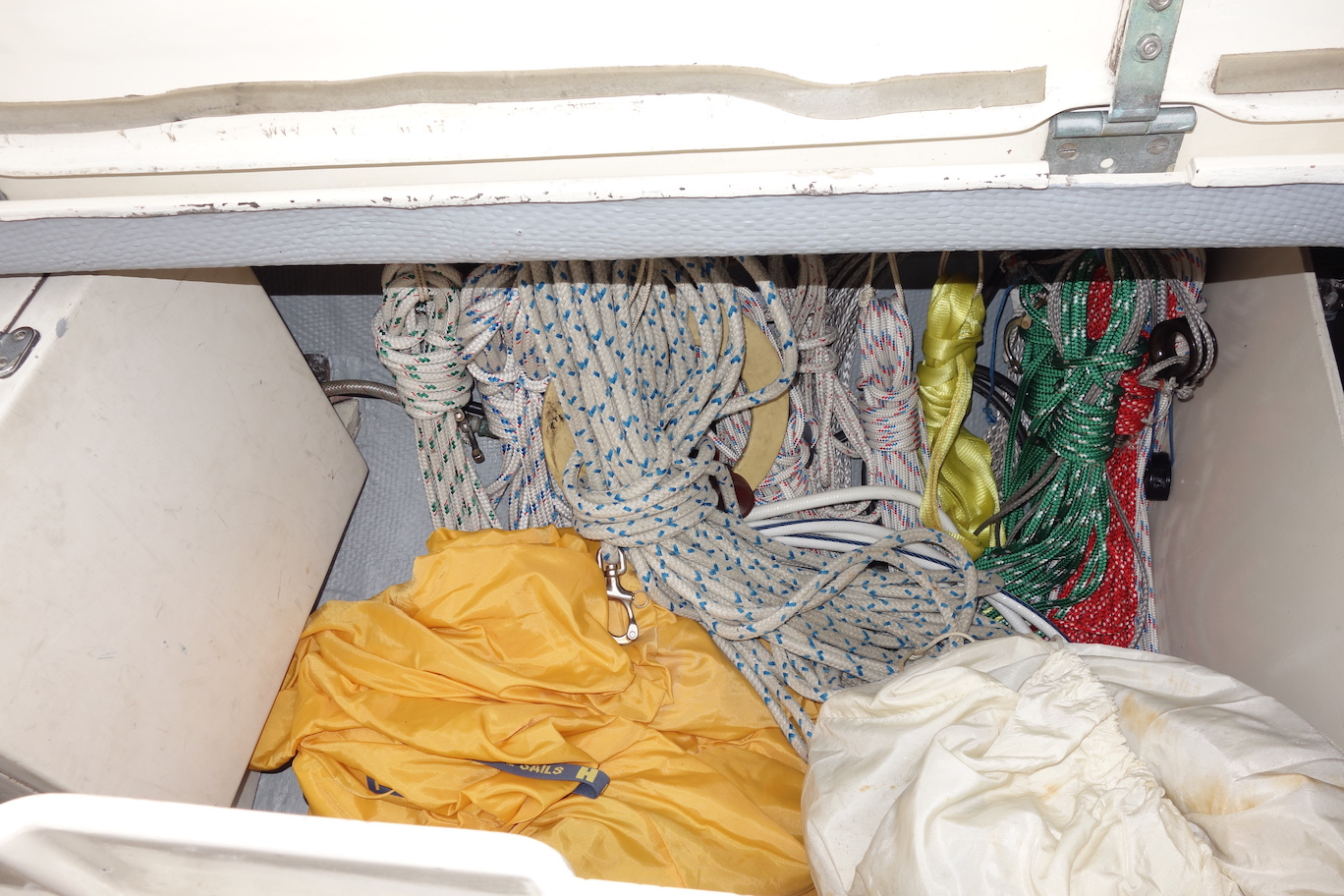 Sail storage in port cockpit locker. Note the very organized line storage on hooks outboard.