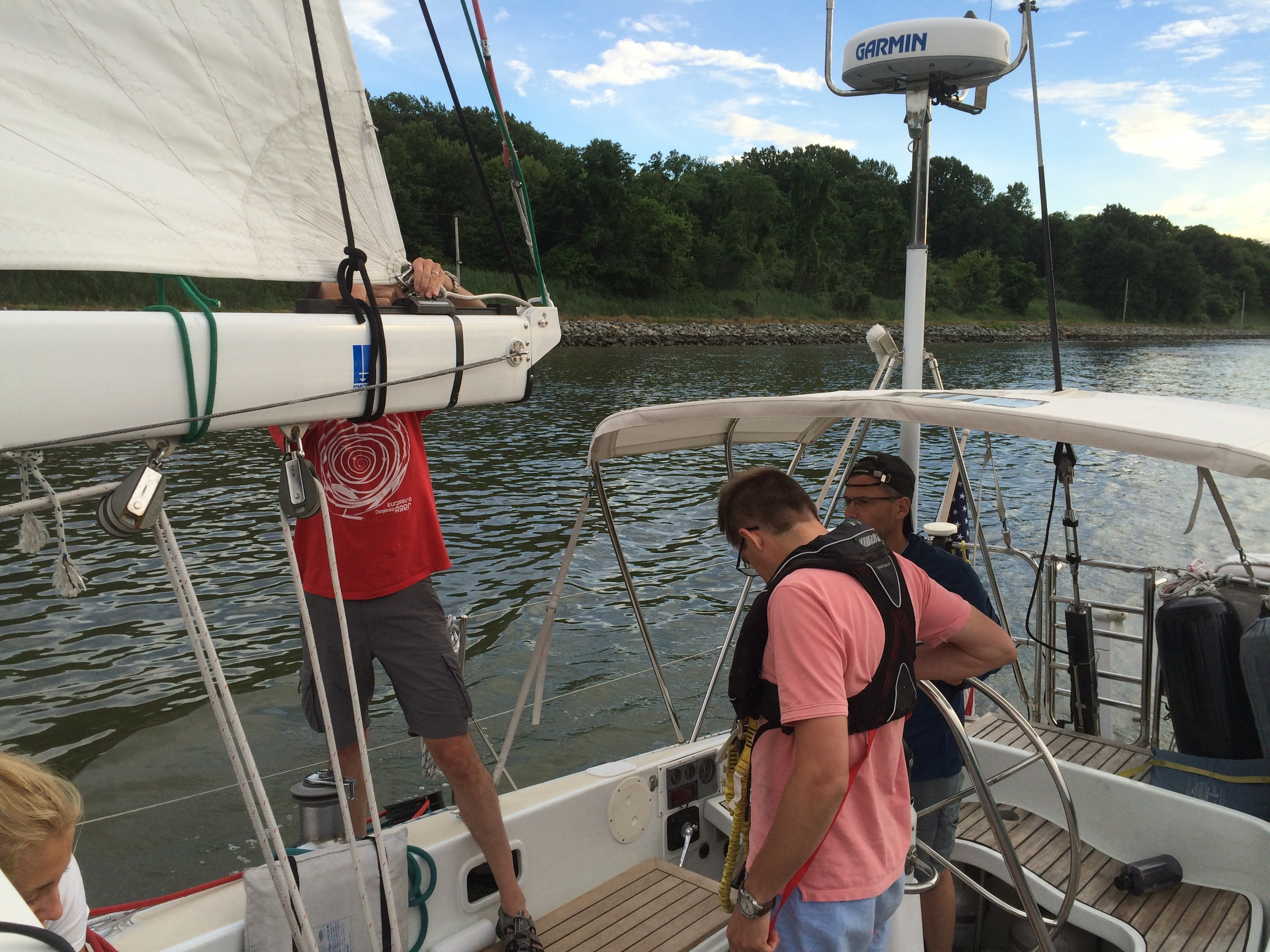 Bruce and the crew fixing the mainsail outhaul shackle in the C&D Canal.