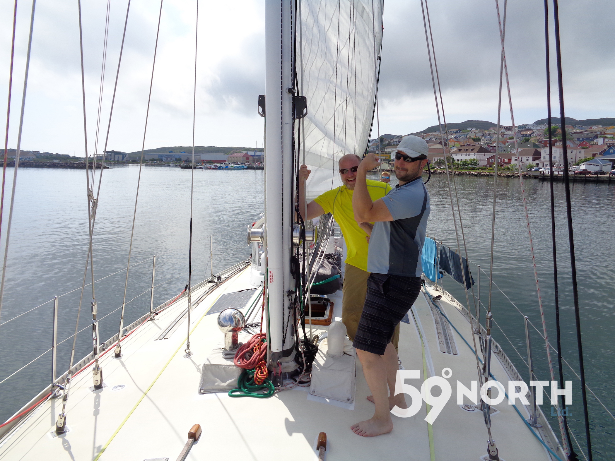 Sun's out, guns out! Leaving St. Pierre under a blue sky! Dan and David ready to hoist the main!