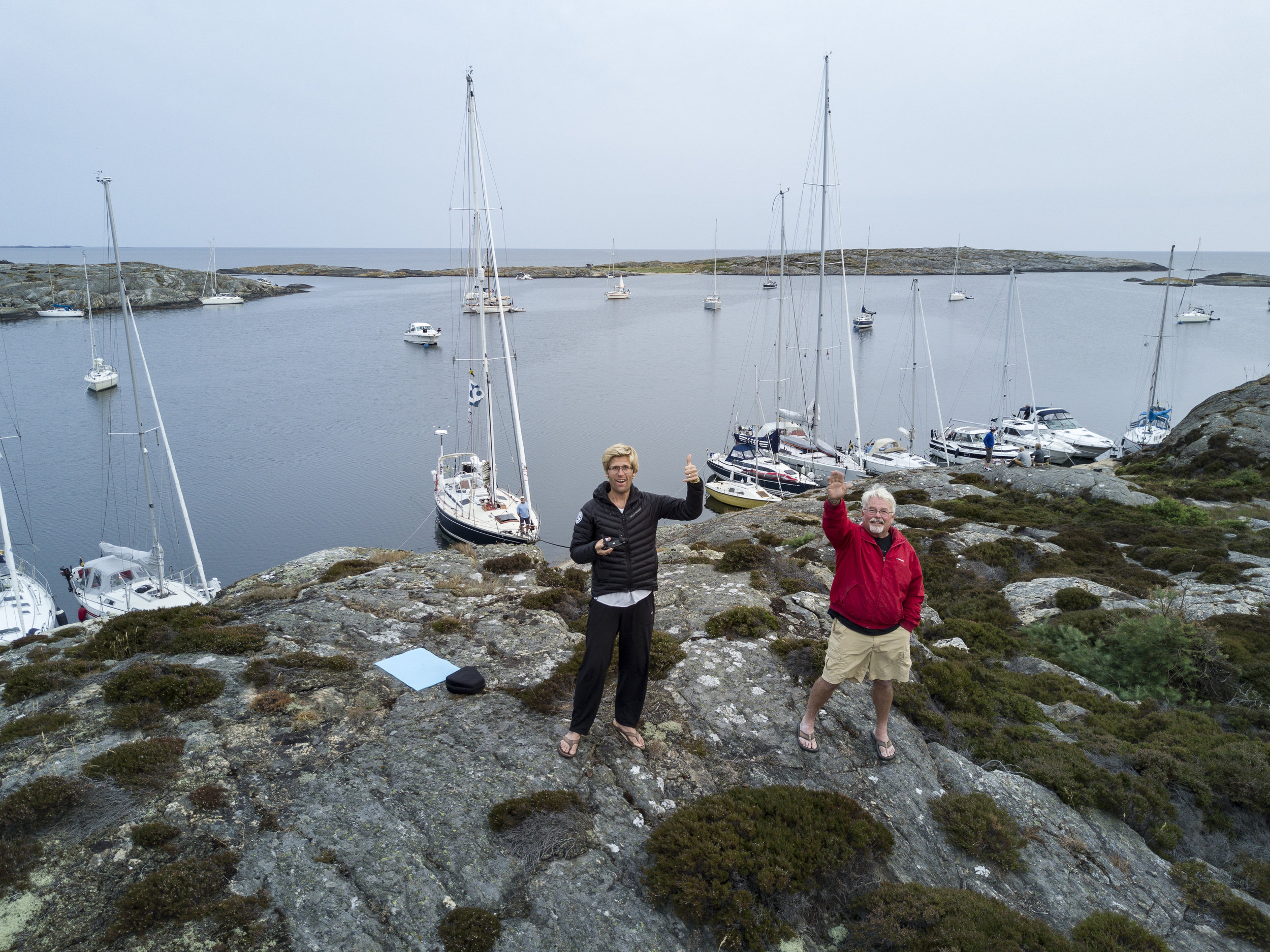 Andy & his dad Dennis flying the drone in Mollön Isbjorn in the background anchored to the cliffs.