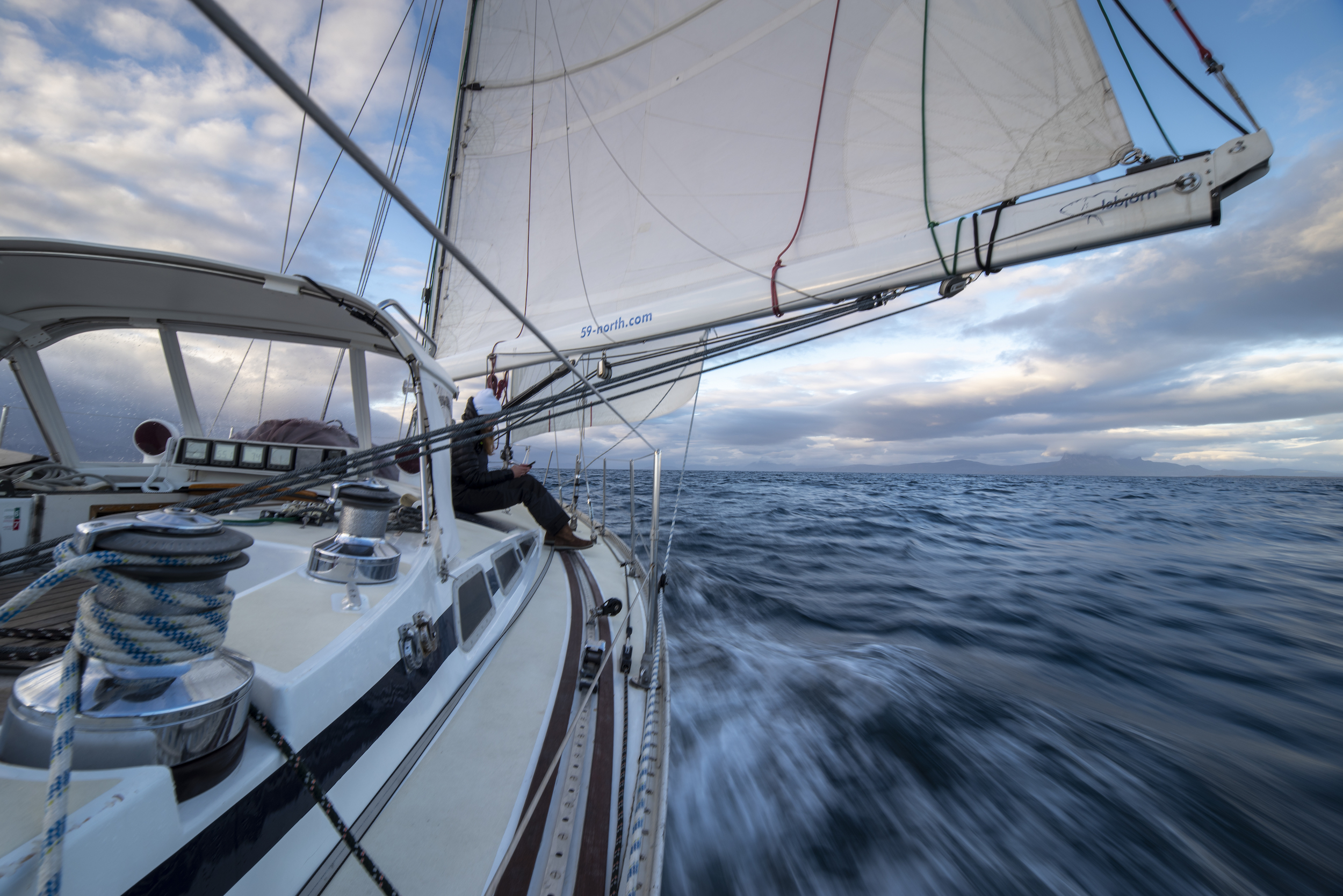 Vanilla sky in the late evening Arctic light sailing downwind in the Vestfjord.