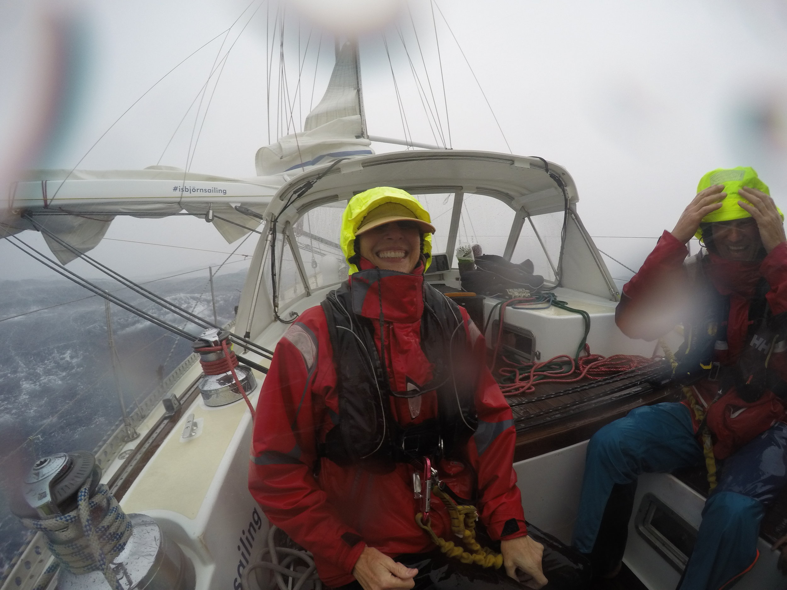 Just after the height of the little storm. The rain really does flatten out the sea, it was raining that hard. Blowing about 35 knots in this photo, (nervous) smiles all around!