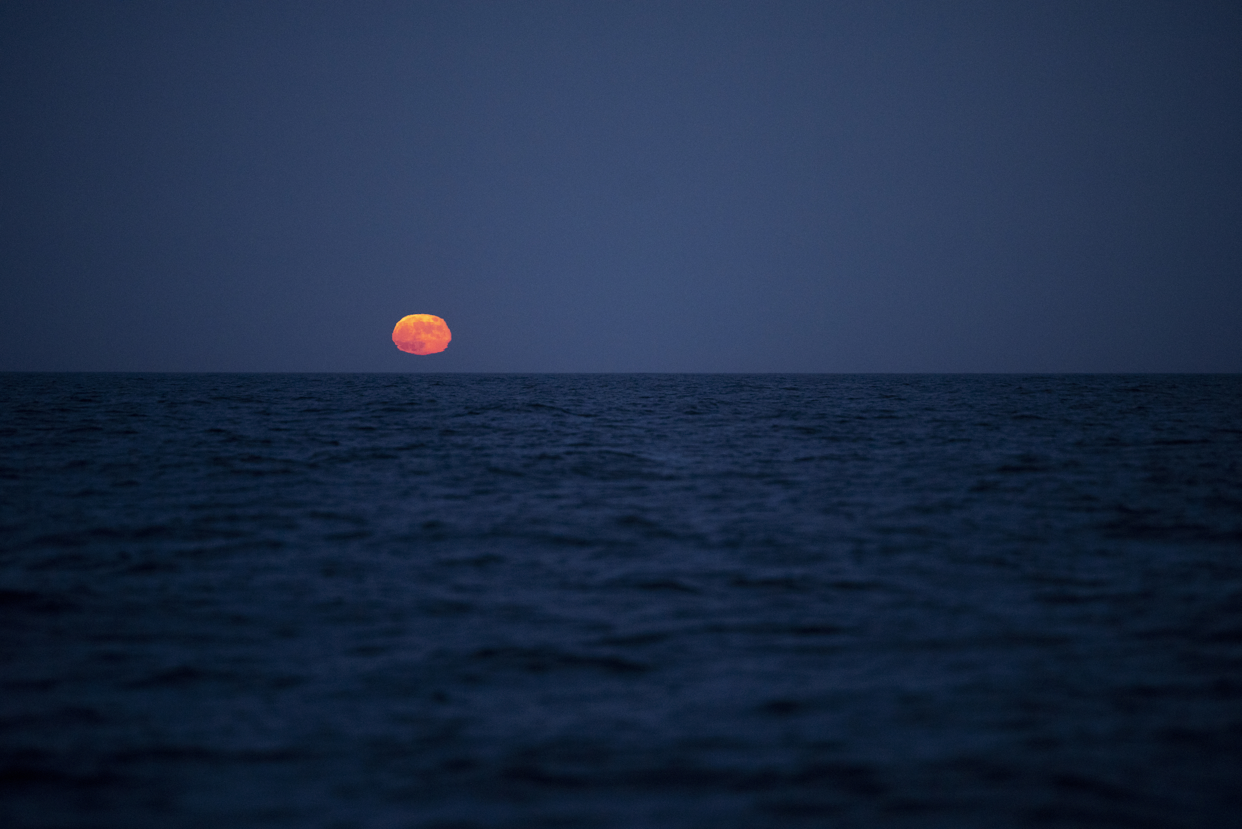 Red moonrise at sea, the refraction in the atmosphere creating an eerie mirage on the horizon.
