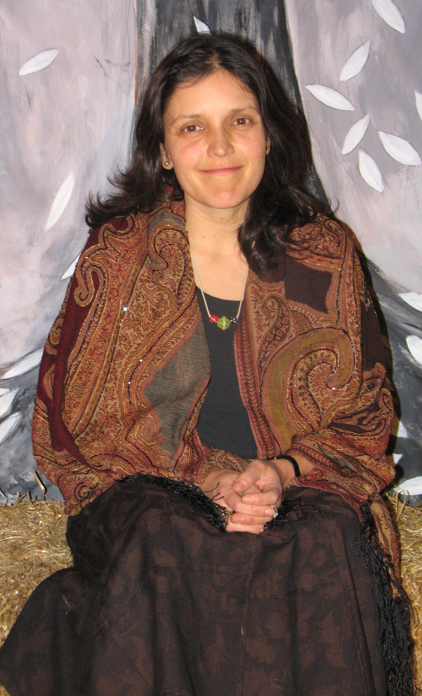 Luz Elena, pronounces LUCE EL  LAY  NAH, sitting in front of the set of The Night Passage, from Gathering in Gratitude, 2010, Painting by John Loggia.
