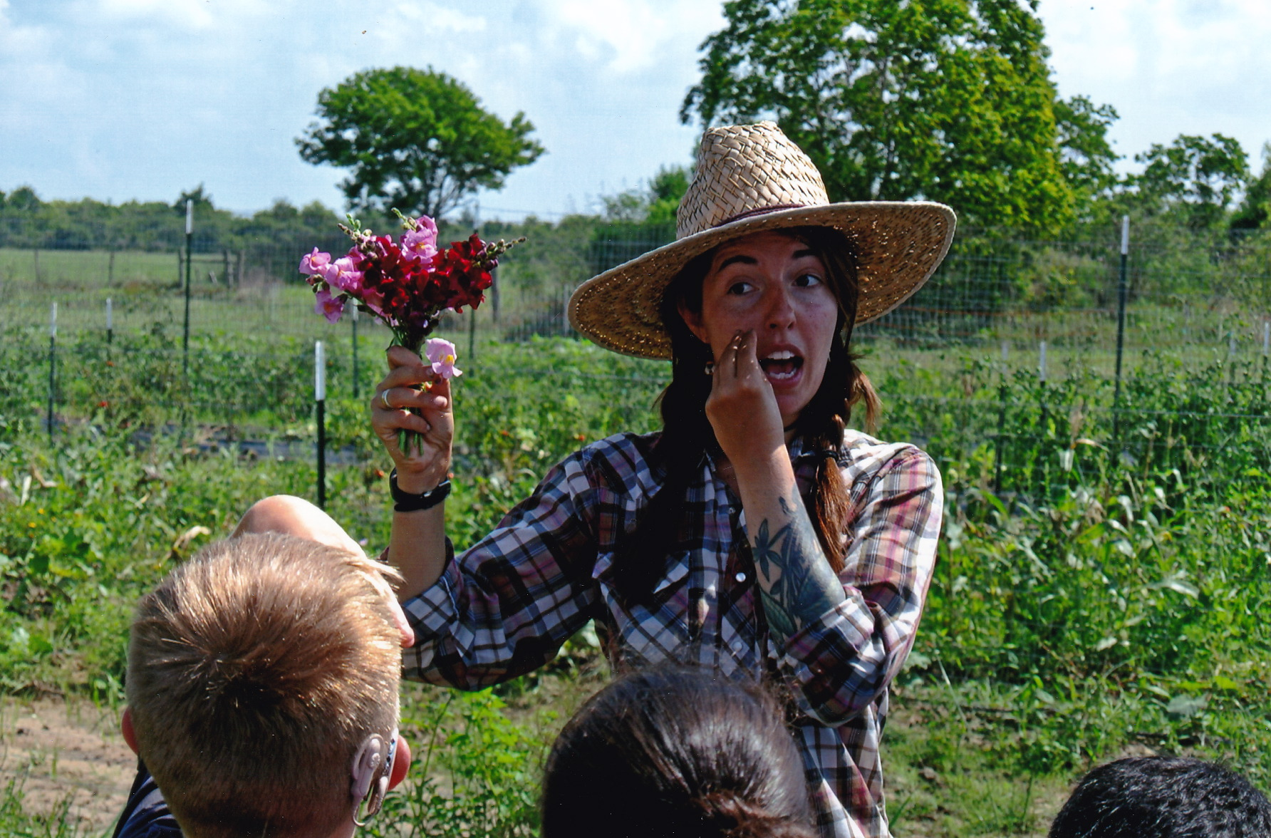 "Farmer Casey signs ""flower"" during a lesson on snapdragons  with students from Goose Creek's Tri-County East Regional School for the Deaf ."