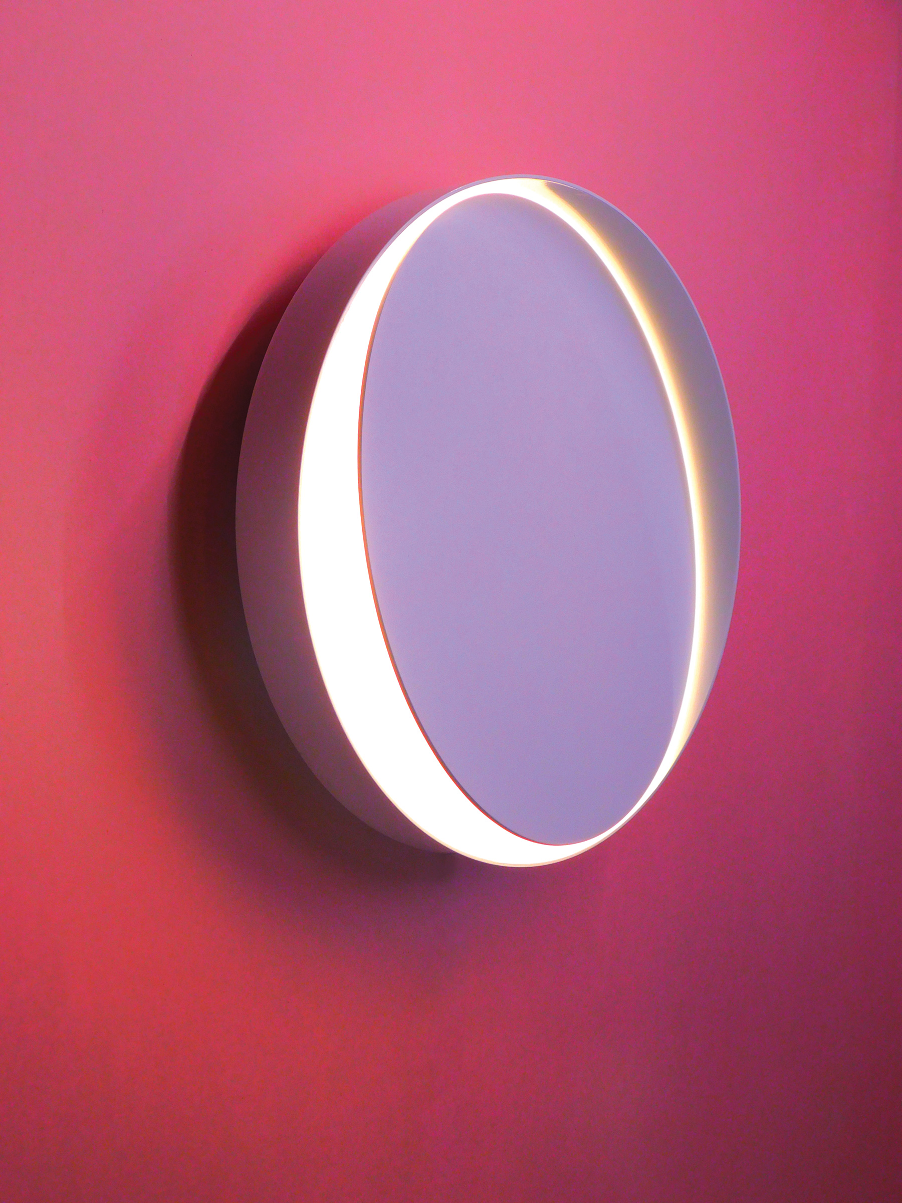 The Horizon wall sconce, by Anony- a minimalist disk with an unbroken ring