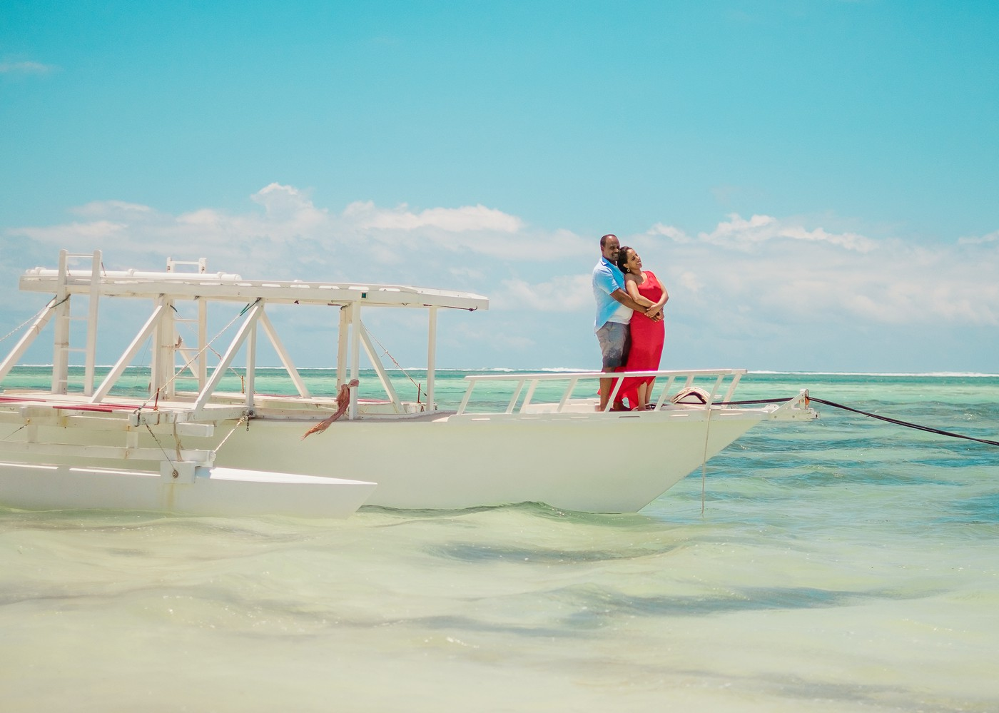 Bride and groom pose for their engagement portraits in front of the colorful sky in the Diani Marine Village.