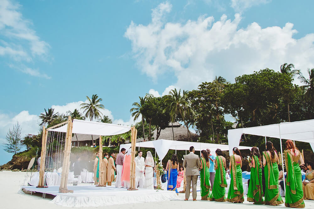 The bride and groom look at each other happily during the ceremony. Diani Beach Destination Wedding  Kenyan coast photographer Destination Wedding Photography Kenyan Wedding Award Winning Fashion Female Destination Kenyan Top Kenya Wedding Photographer