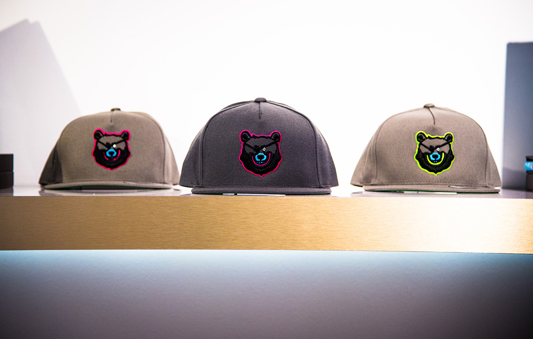 Snapbacks from the Launch Collection feature Bash the Pirate Bear. A gradation of grey caps stitched with 3D embroidery in contrasting pink and neon colors. Edition of 100, number stitched on the inside.  Shop.