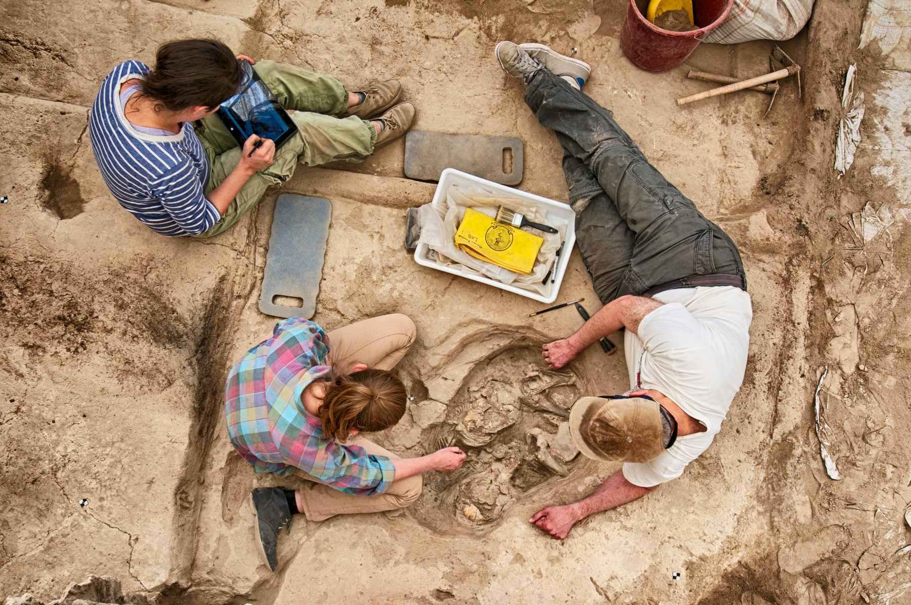 Chris helps Kasia with a skeleton removal in a Building 80 burial (South Area) as Justine logs details.