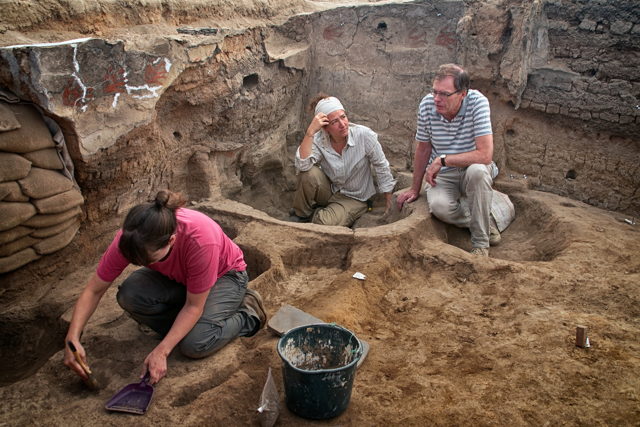 Burcu and Ian discuss excavation plans in Building 77 (North Area) during the last days of the 2013 season. In the foreground, Renata cleans her area for a photo.