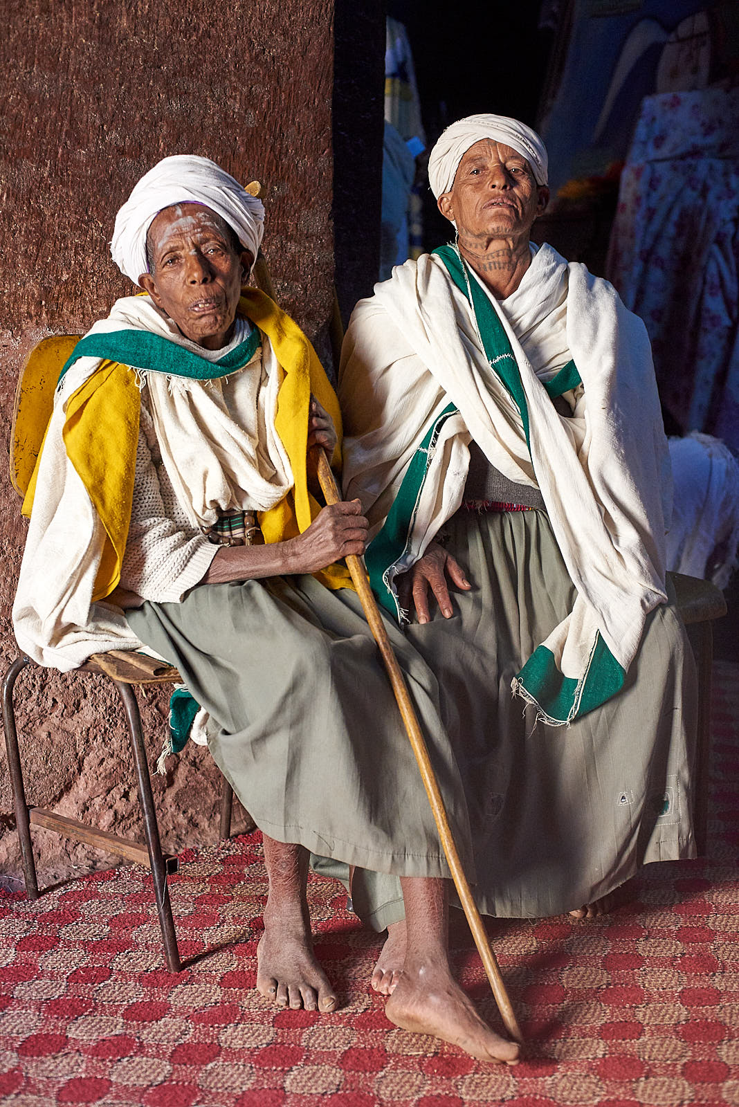 An Ethiopian Orthodox priest and pilgrim rest together after praying inside the Church of Saint George, Lalibela, Ethiopia.