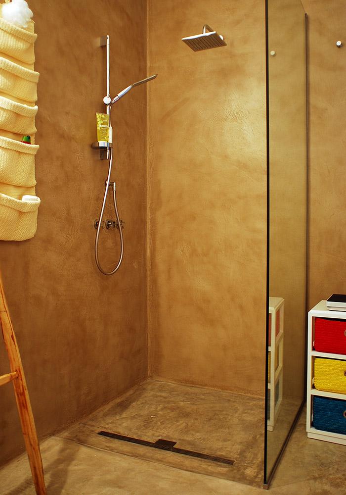 Pavimento in calcestruzzo nuvolato e pareti rivestite in resincementizio