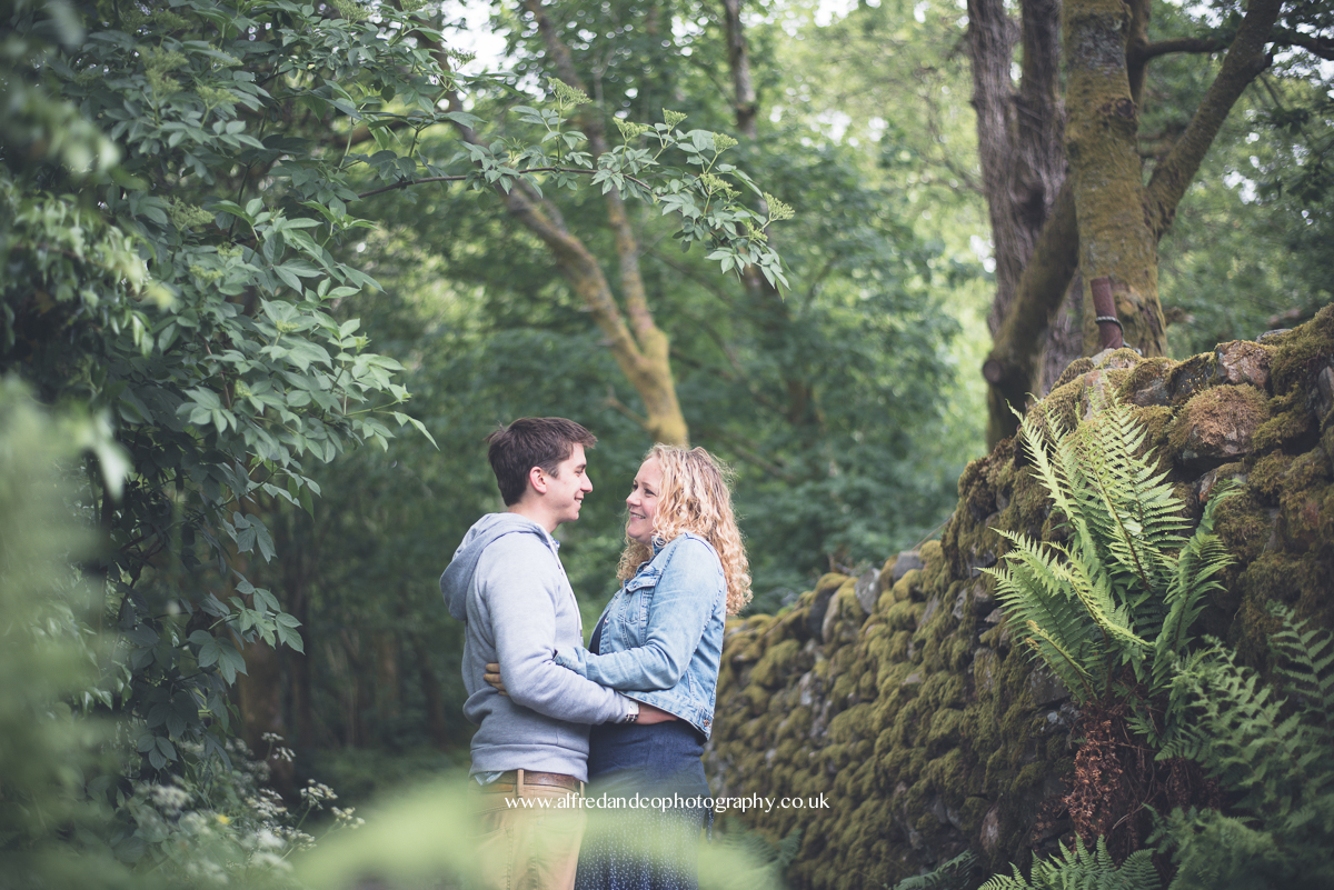couple posing between trees
