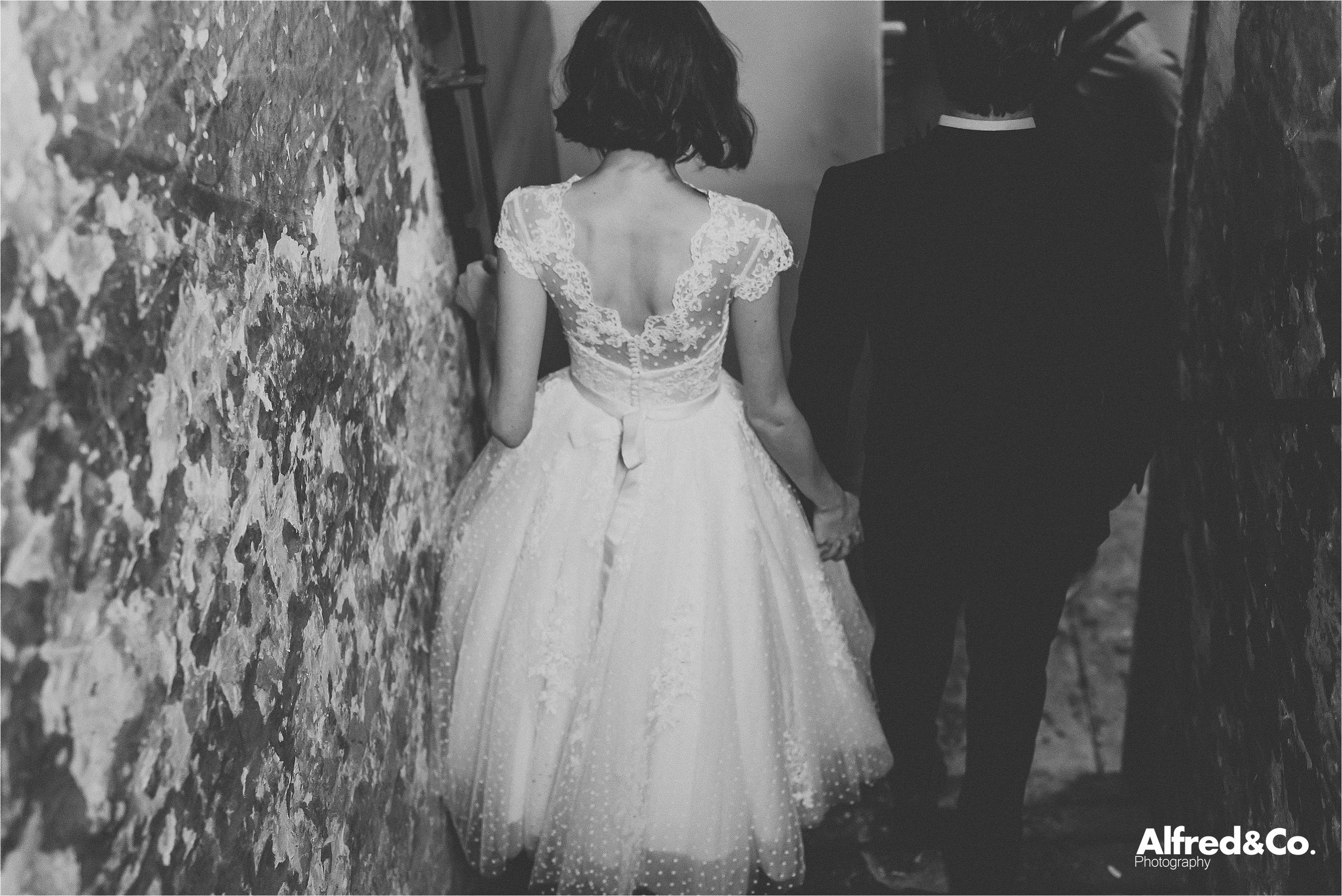 quirky bride and groom walking down stairs at holmes mill