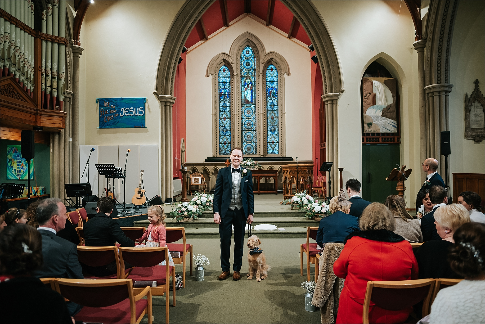 groom and dog at the top of the aisle in church for wedding