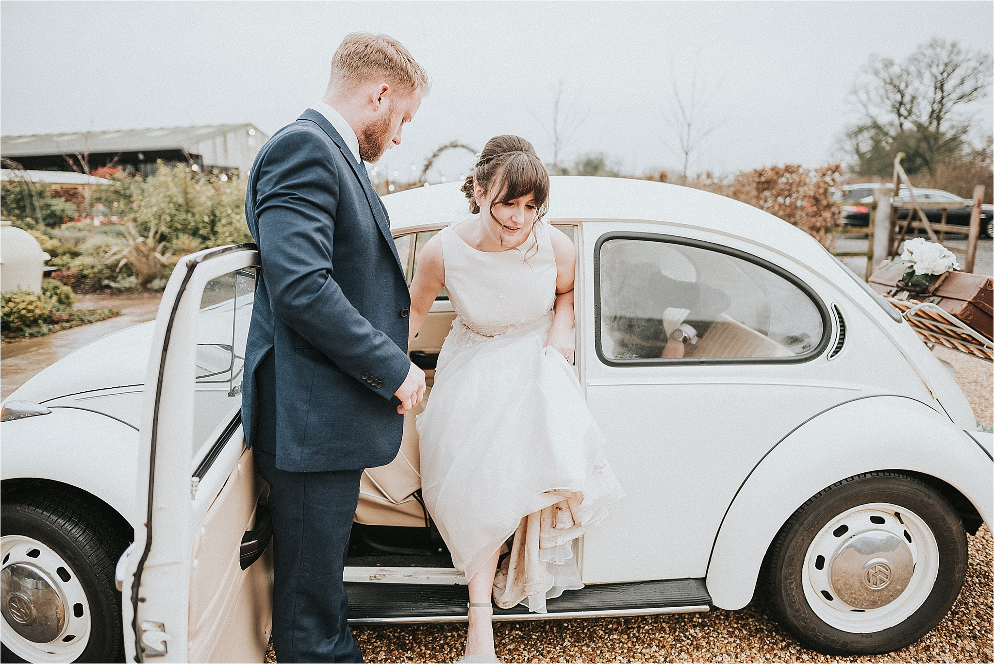 bride stepping out of vw beetle at owen house wedding barn