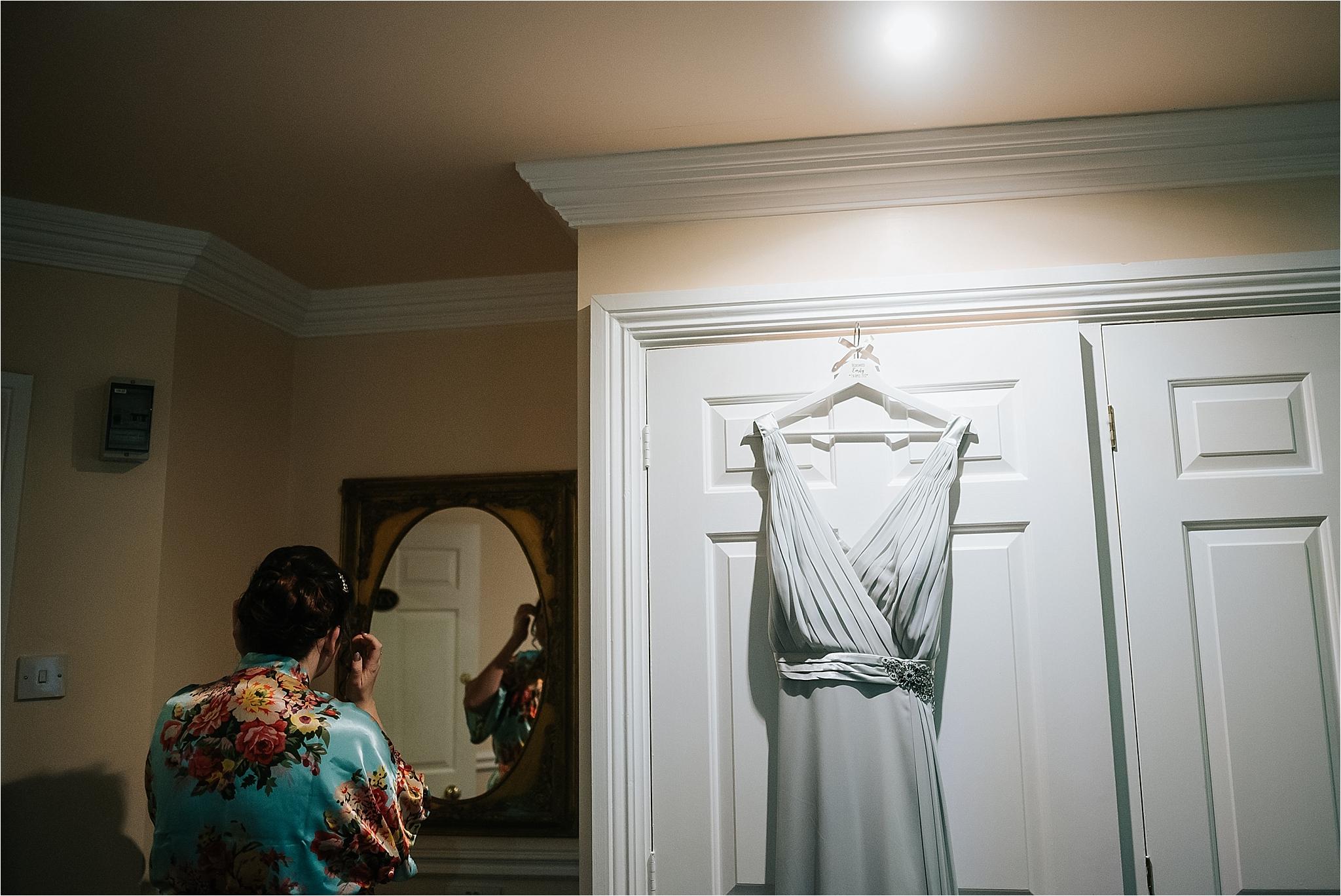 bridesmaid dress hangs in bridal suite