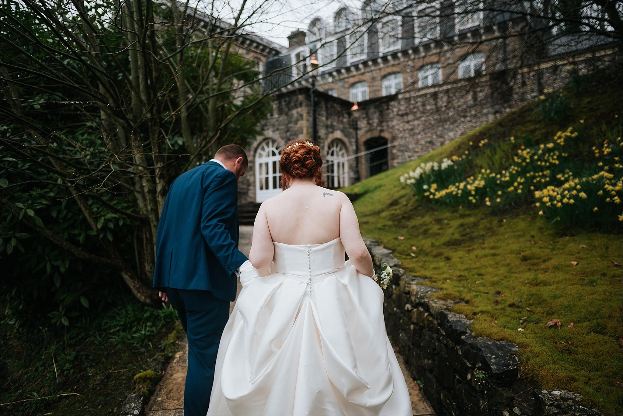 bride and groom walk towards grange hotel
