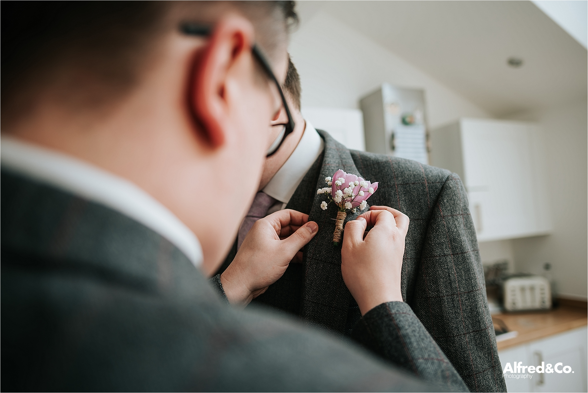groomsmen putting on buttonholes