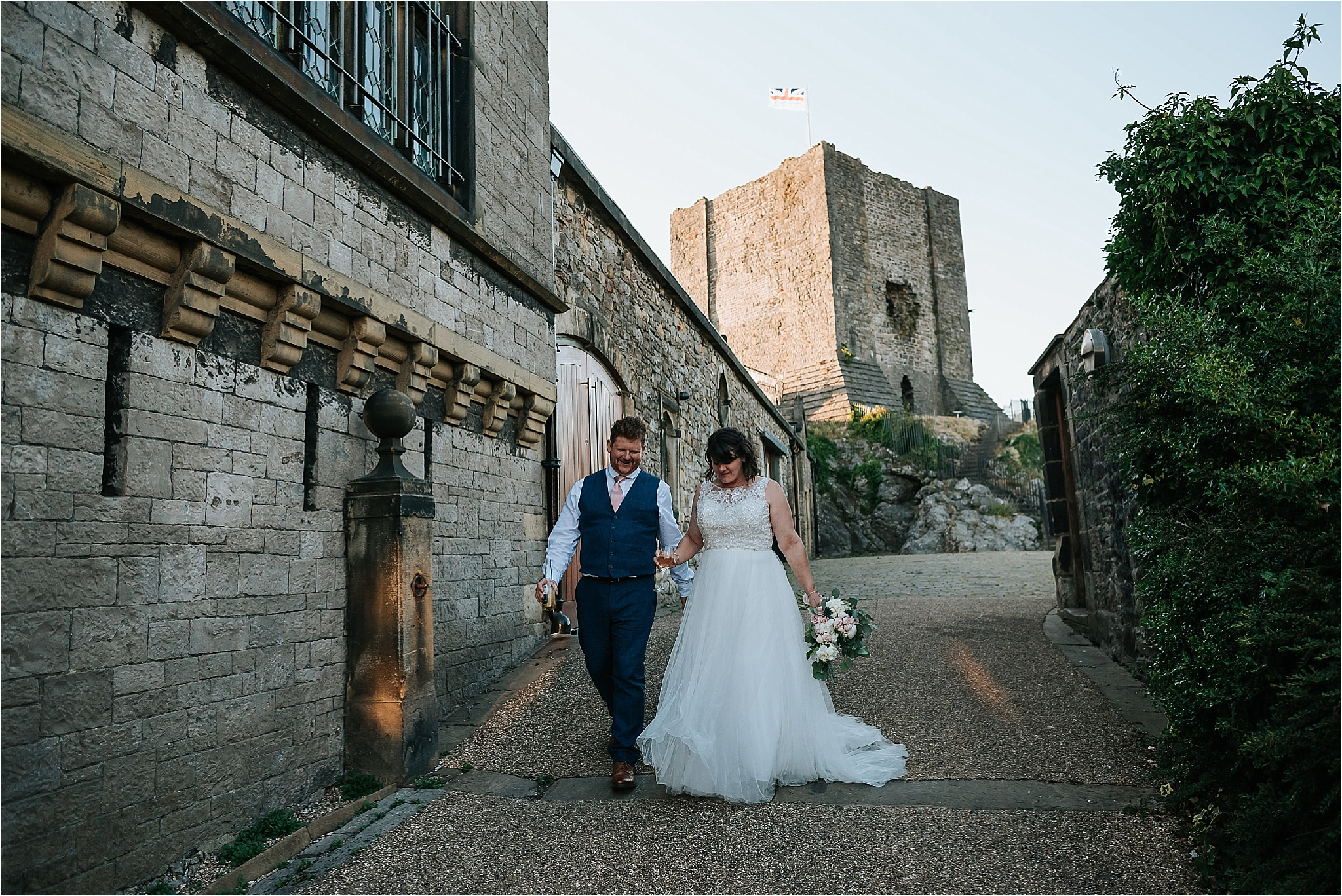 bride and groom walking down from clitheroe castle