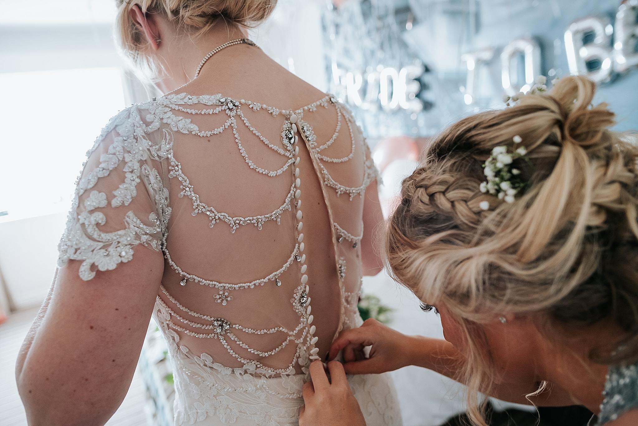 bride having her dress done up