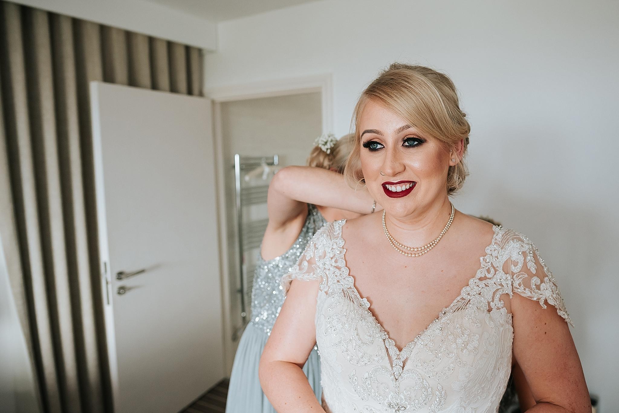 bride getting wedding dress on before wedding