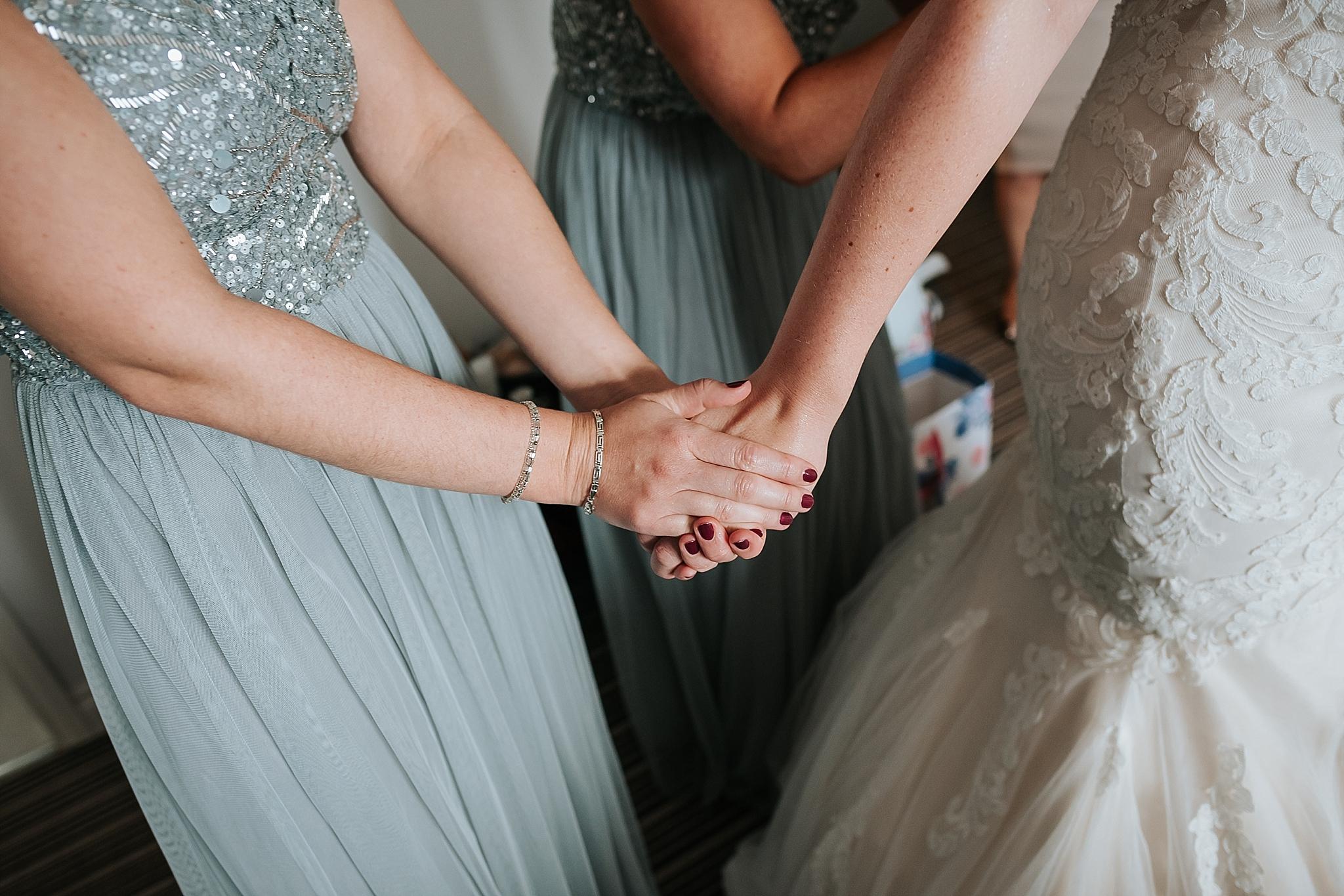 bridesmaids holds brides hand before wedding