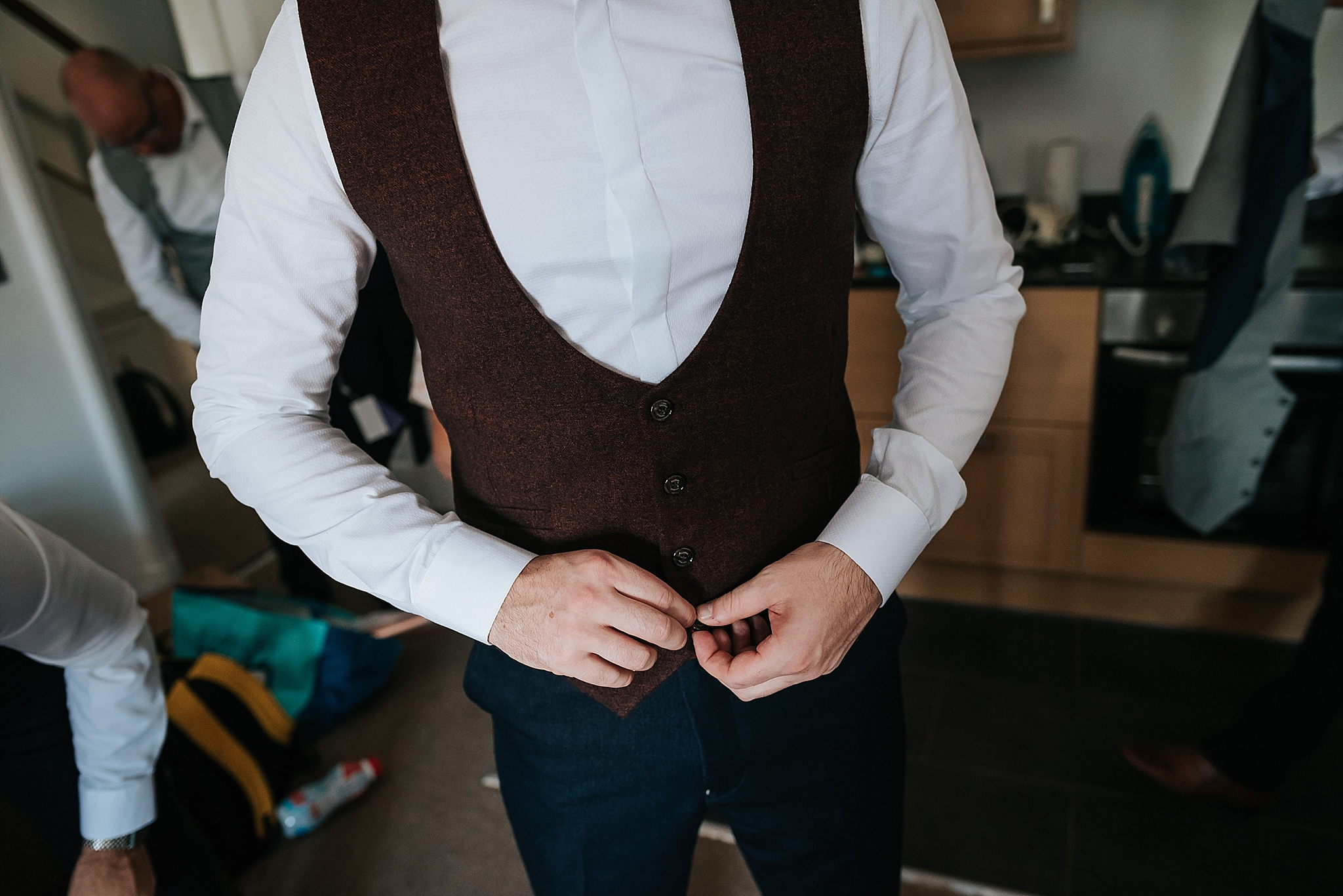 groom puts his suit on