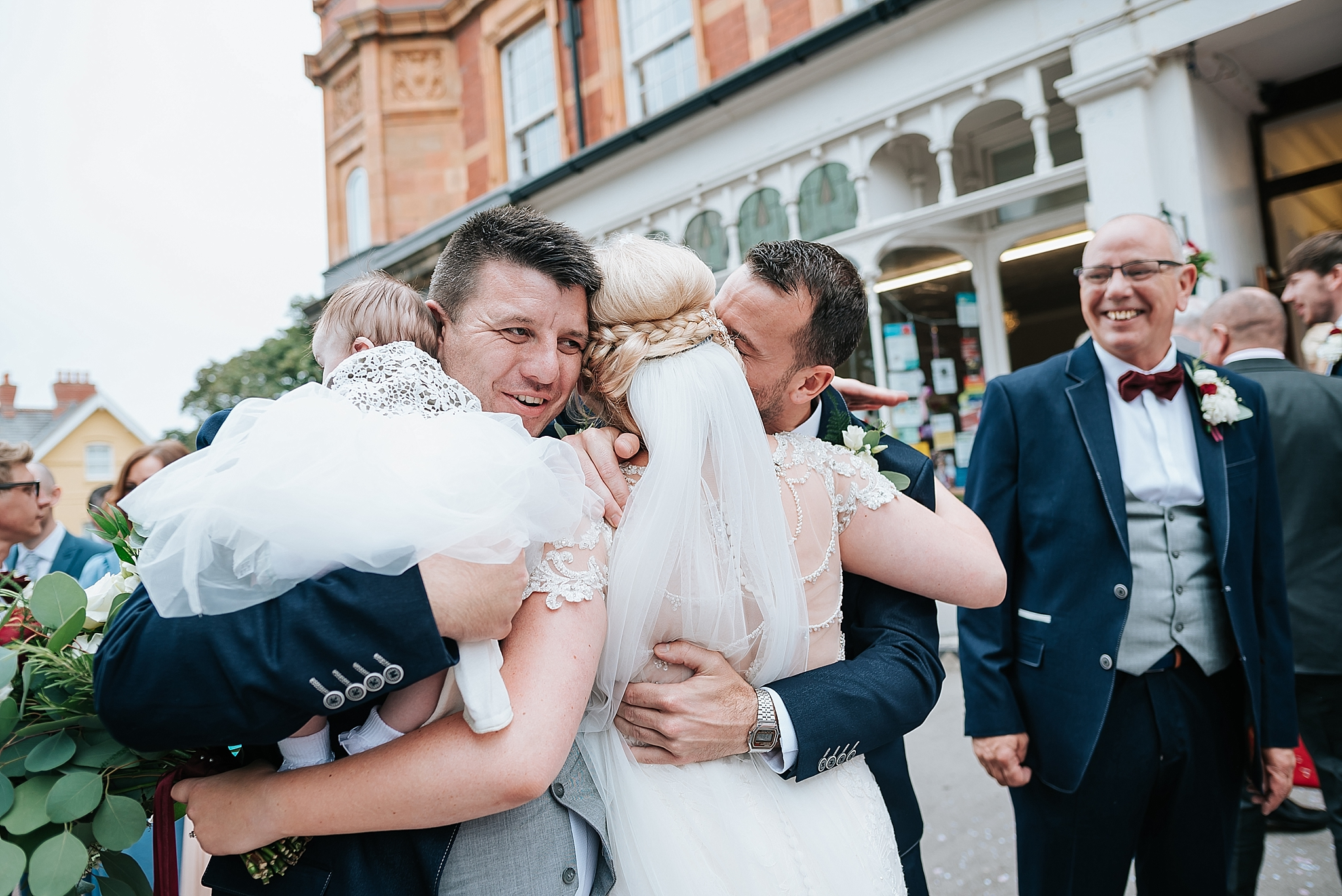 bride hugs her family after wedding celebration at st annes palace