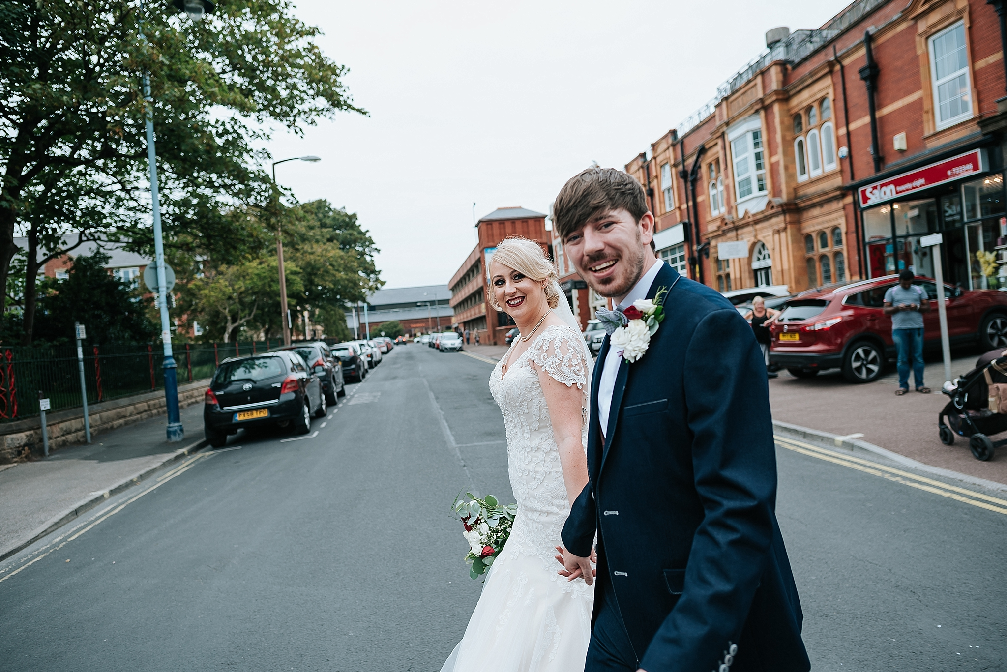 cool bride and groom walking across the road in st annes