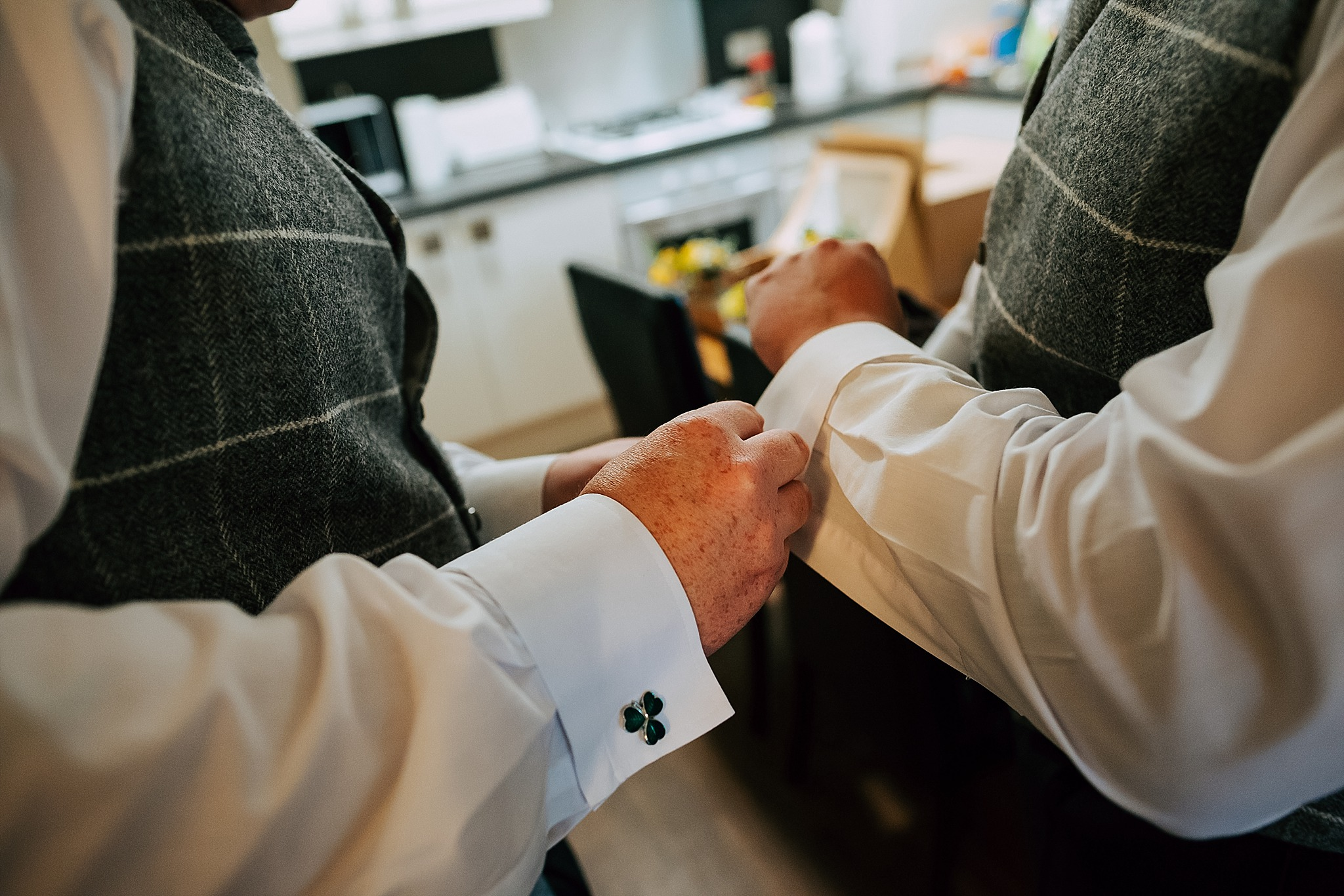 groom and best man put cuff links on