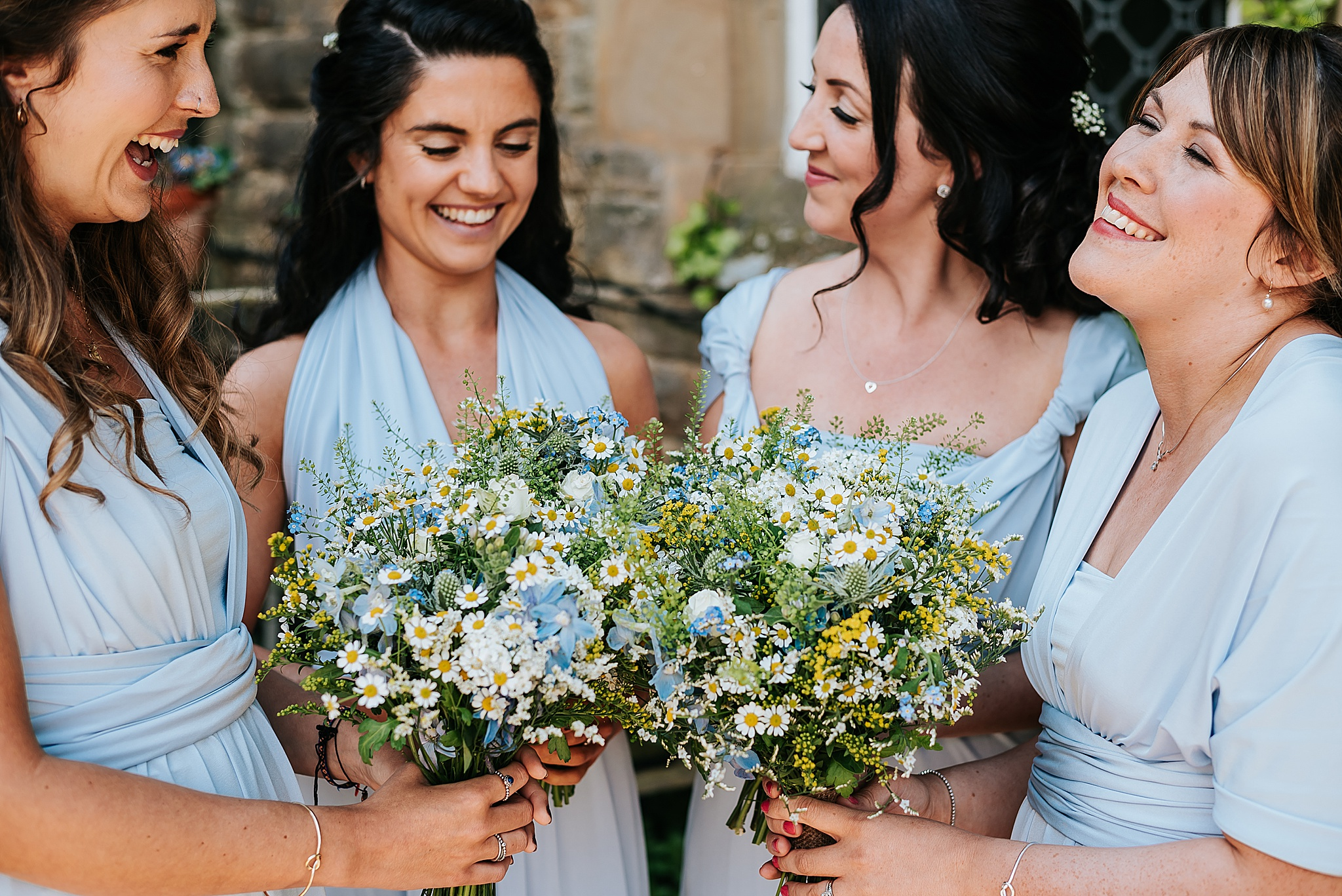 bridesmaids in blue dresses with spring blue and yellow flowers