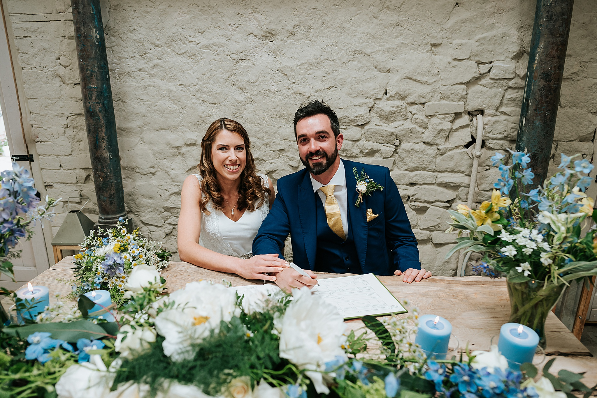bride and groom sign register at lancashire wedding venue
