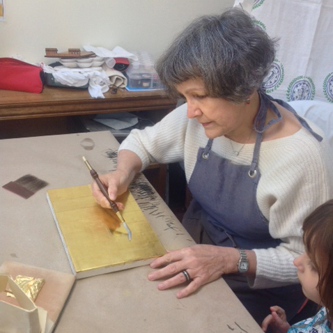 The gilder at work, burnishing the gold leaf with an agate tool.