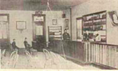 Library Reading Room on South Main Street, Professor Adolf Peck leans against the counter. (Source: Library Archives)