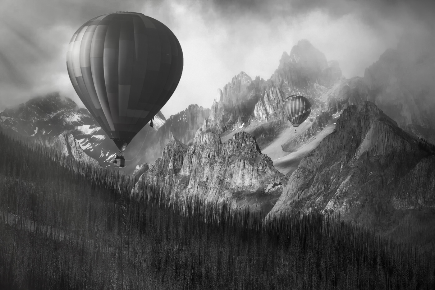 This dynamic image is contrasted both in tone and subject. the fragile round balloons and jagged stormy peaks.